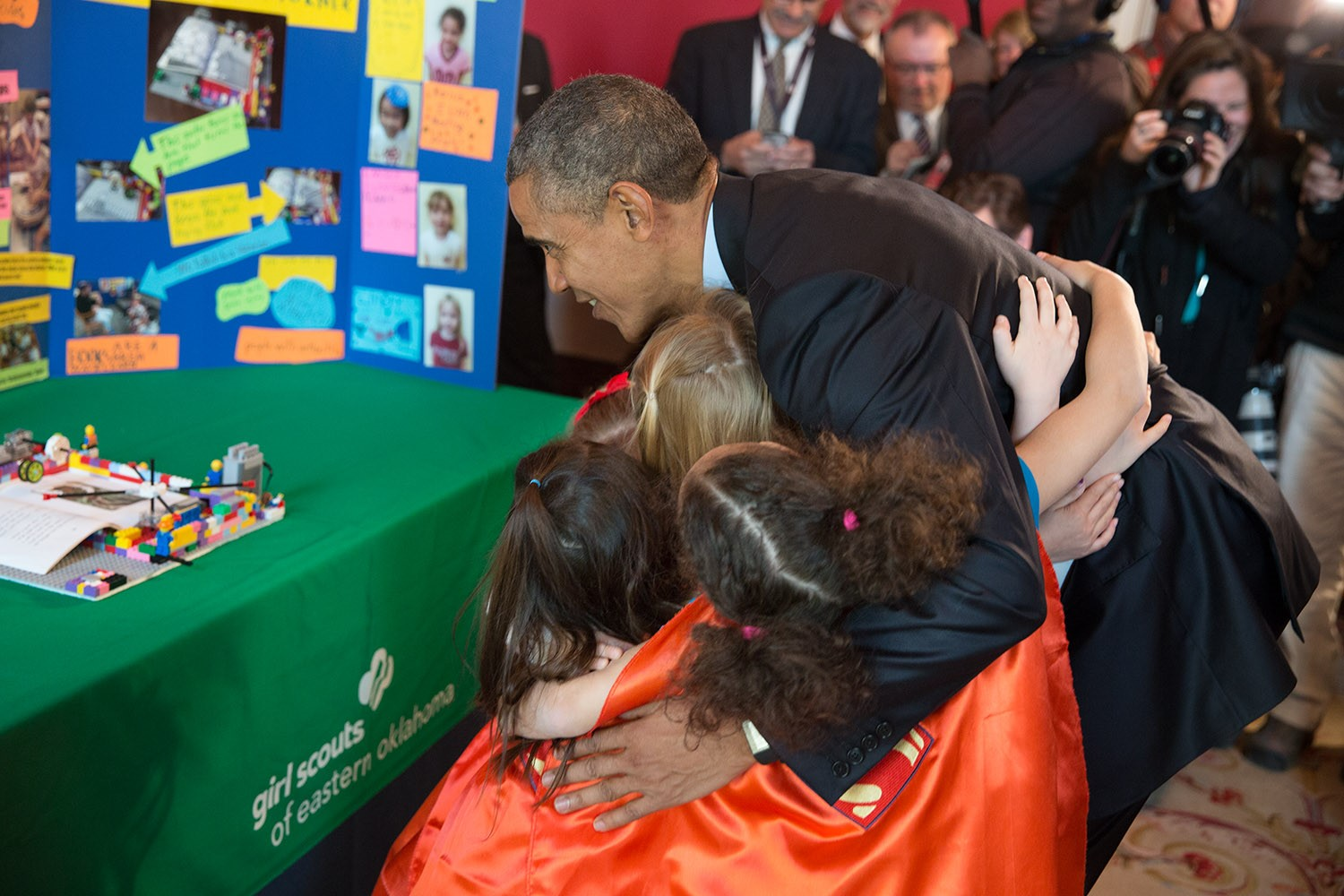 President Barack Obama hugs Emily Bergenroth, Alicia Cutter, Karissa Cheng, Addy O'Neal, and Emery Dodson, all six-year-old Girl Scouts, from Tulsa, Oklahoma after viewing their science exhibit during the 2015 White House Science Fair celebrating student winners of a broad range of science, technology, engineering, and math (STEM) competitions, in the Red Room, March 23, 2015. The girls used Lego pieces and designed a battery-powered page turner to help people who are paralyzed or have arthritis. (Official White House Photo by Pete Souza)