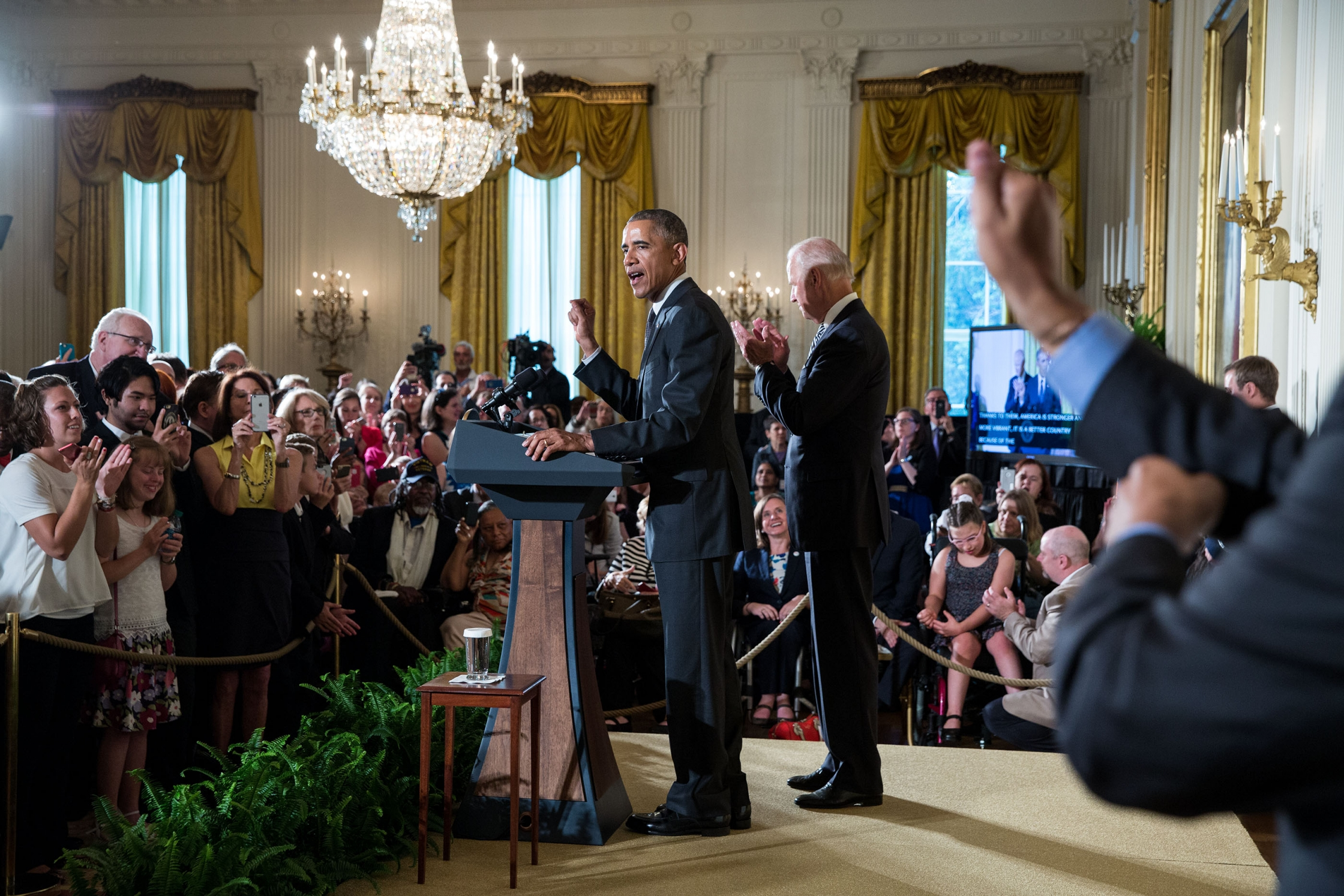 An interpreter signs in the foreground while President Barack Obama, with Vice President Joe Biden, delivers remarks during a reception for the 25th anniversary of the Americans with Disabilities Act (ADA) in the East Room of the White House, July 20, 2015.