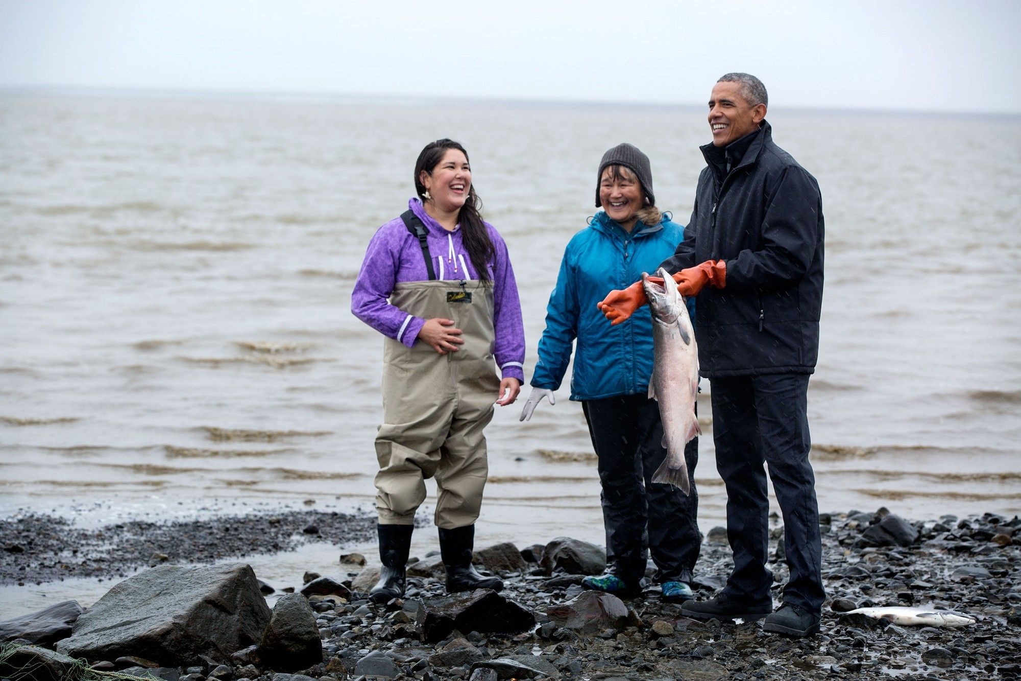 Getting a hands on demonstration from salmon fisherwomen. (Official White House Photo by Pete Souza)