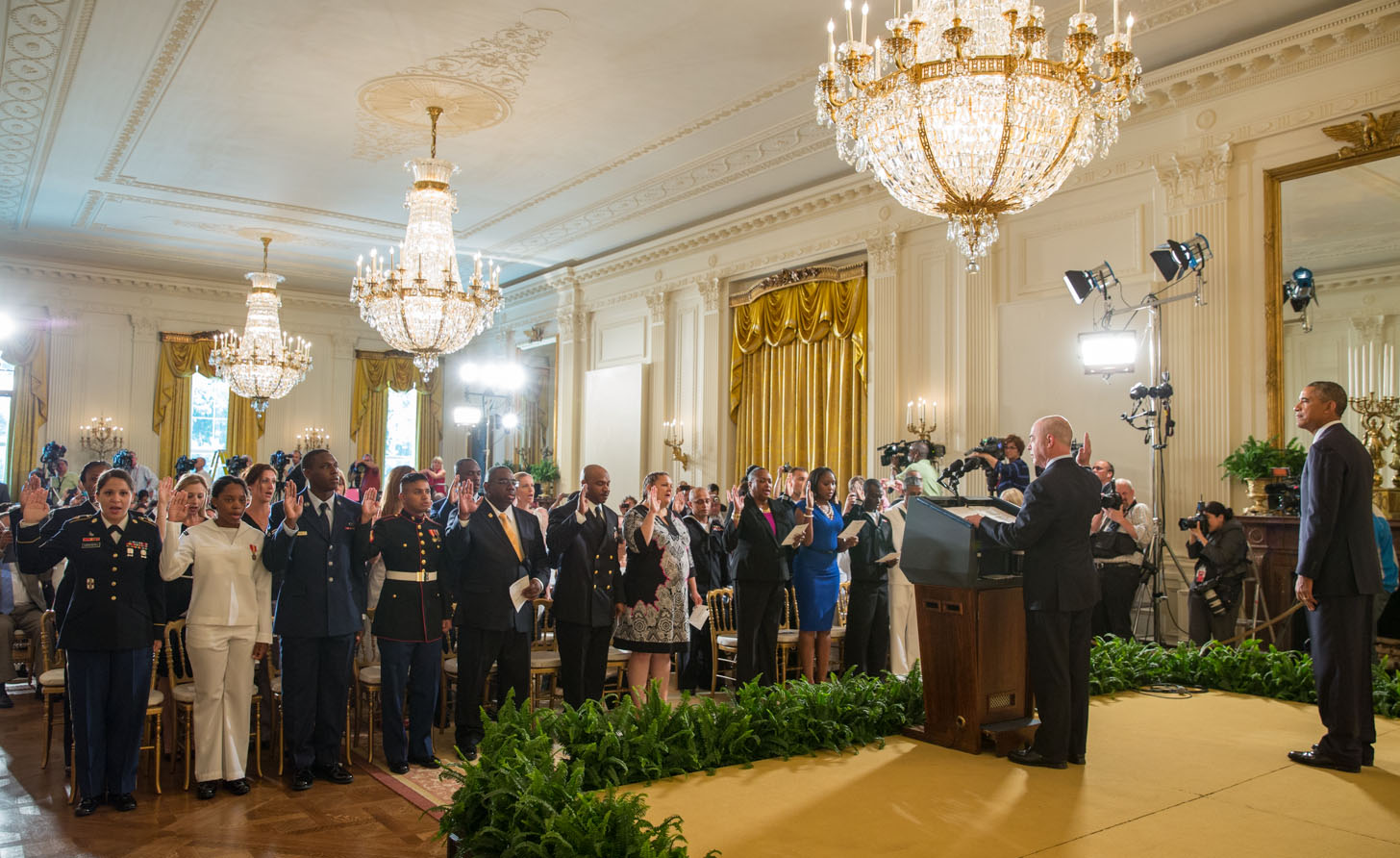 President Barack Obama listens as Deputy Secretary Alejandro Mayorkas, Department of Homeland Security administers the Oath of Allegiance during a naturalization ceremony